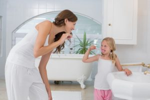 Mom making daughter wash teeth