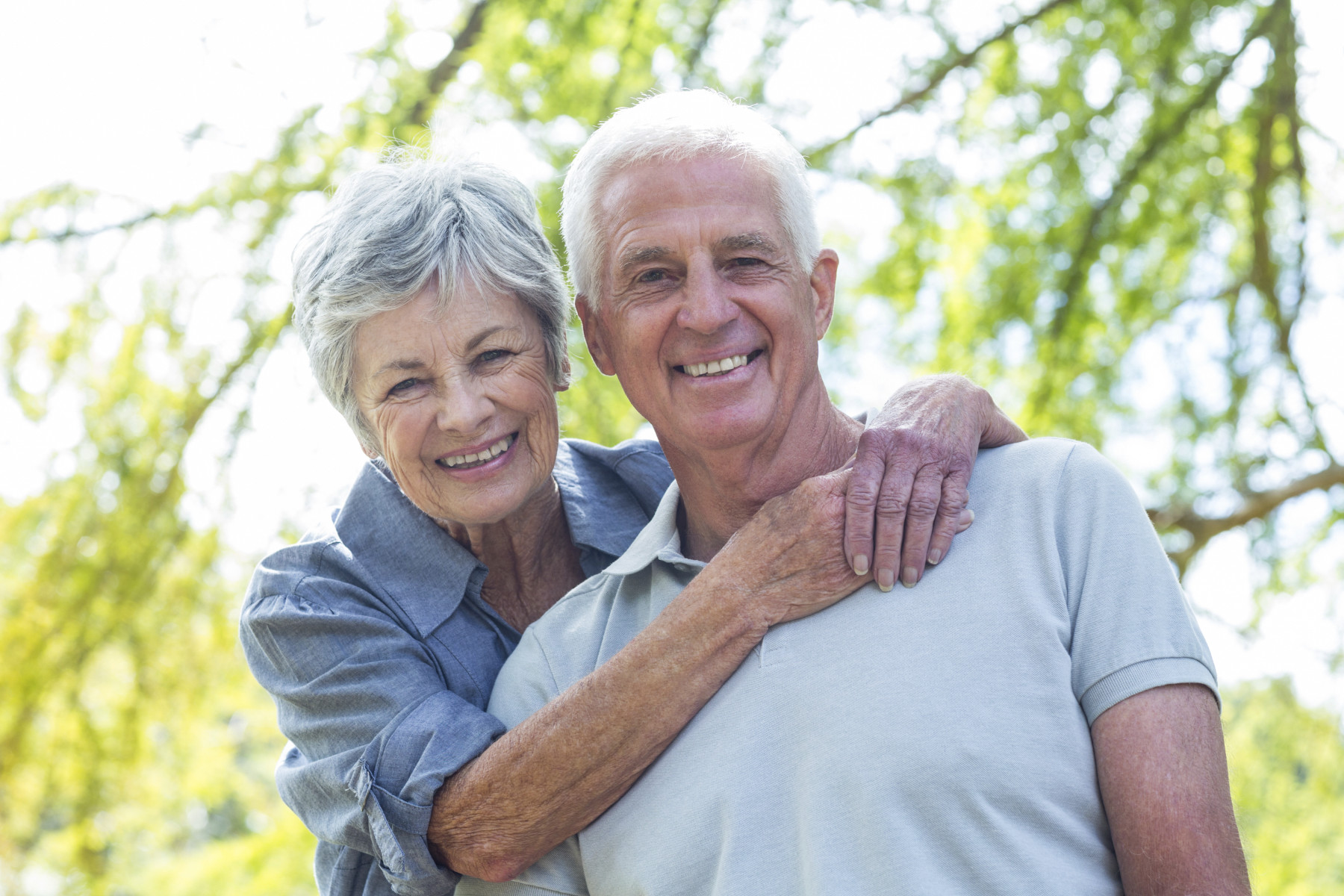 Gray haired couple sitting, hugging, and smiling happily.
