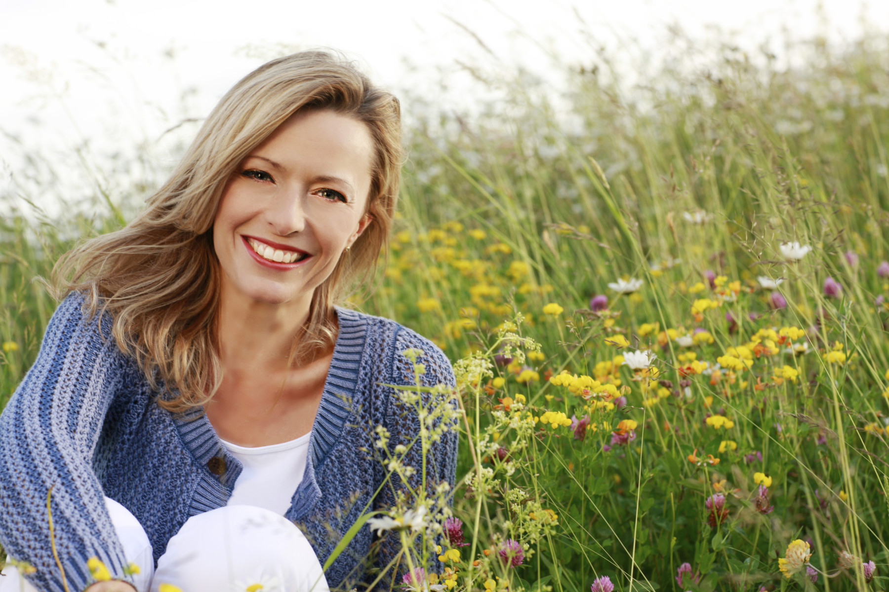 Woman with a bright white smile sitting in a meadow