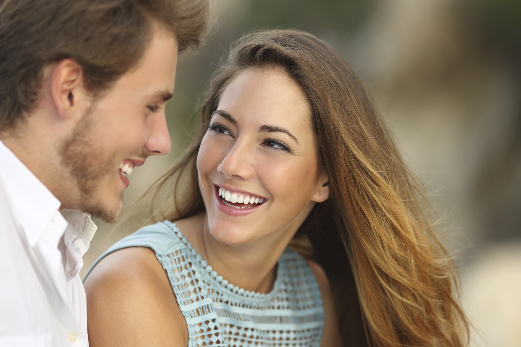 A young couple looking at each other smiling