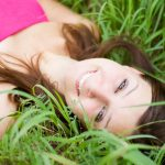 A woman laying in the grass smiling