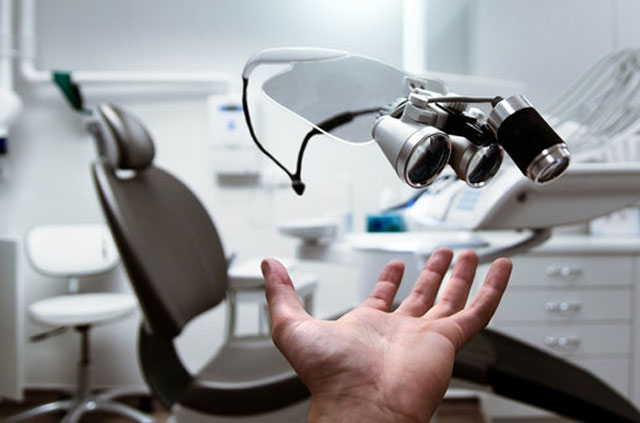A dental examination room in the background with a hand reaching for equipment in the foreground